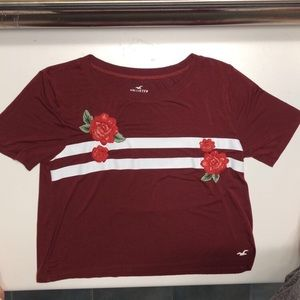 A burgundy shirt with white stripes and flowers